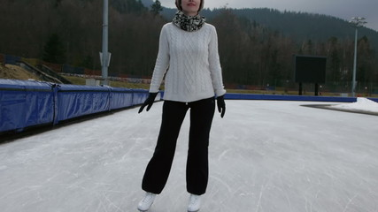 woman figure skating at an open outdoor speed skating rink appro