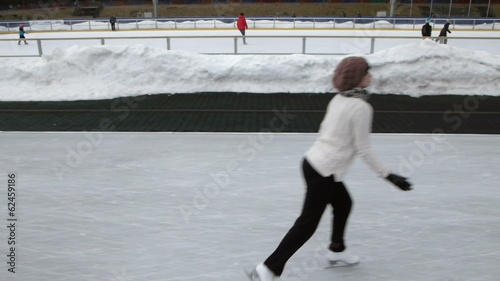 woman figure skating at an open outdoor speed skating rink side