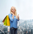 smiling woman with shopping bags showing thumbs up