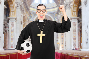 Male priest holding football and cheering in a church