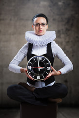 Business lady in ruff collar with a clock looking at camera