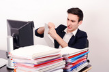 Angry unhappy business man tearing up paper work from a big pile