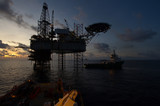 Silhouette of offshore jack up rig at sea during sunset