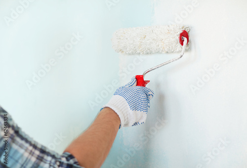 close up of male in gloves painting wall