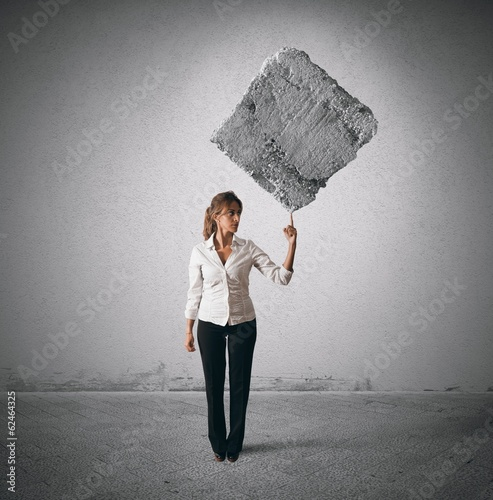 Businesswoman lifting heavy rock