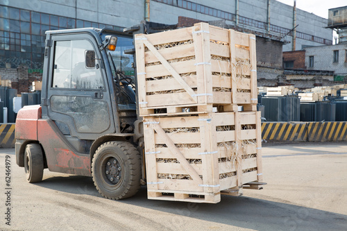 Factory forklift truck transporting wooden boxes