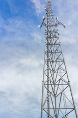 Tall steel cellphone tower structure,blue sky with clouds.