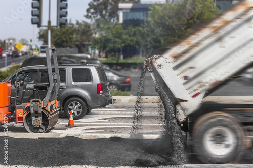 Road paving repairs on suburban city street.Dump truck,asphalt.