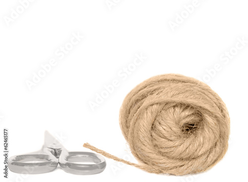 Loose coil of hemp rope,closed metal scissors,isolated.