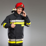 Fireman holding smart phone and showing thumb up.
