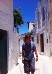 man in a hat walking the street of greek town