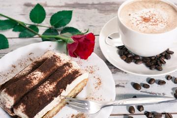 Tiramisu und Cappuccino serviert mit einer Rose