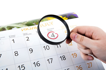 Magnifying glass in hand and the wall calendar