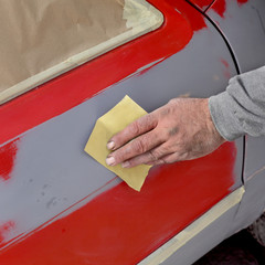 Car painting, ready for repaint, worker sanding primer