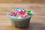 beautiful muffins decorated with spring flower on vintage wooden