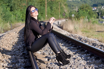 Young beautiful woman sitting on a railroad