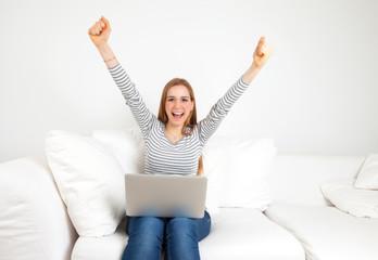 Junge Frau mit Notebook auf dem Sofa freut sich
