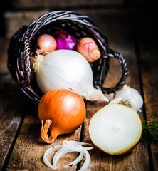 Colorful onions in the basket on rustic wooden background