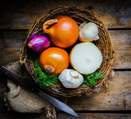 Colorful onions and garlic in the basket on rustic wooden backgr