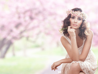 Portrait of a beautiful blonde woman with flowers in her hair.