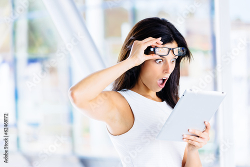 Surprised modern businesswoman with tablet
