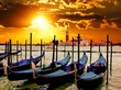Vibrant sunrise over the lagoon of Venice, Italy with gondolas