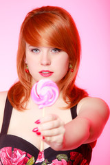 Sexy woman showing candy. Redhair girl giving sweet lollipop