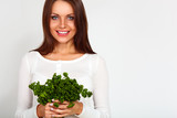 beautiful girl holding two bunches of parsley near the face
