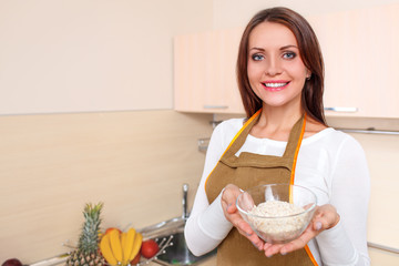 happy young woman at kitchen holding plate of oatmeal