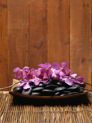 bowl of Spa stones and branch pink orchid on mat