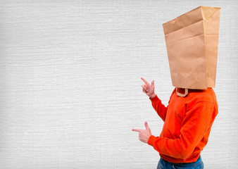 pointing young man in ecological paper bag on head