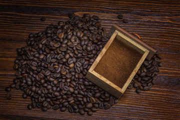 coffee beans and ground on wooden background