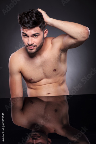 naked young man with hand on his head