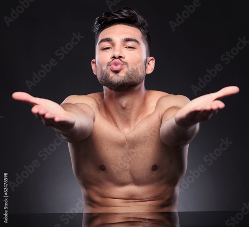 naked young man blows kisses