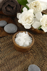 Bowl of spa salt and gardenia and stones on mat