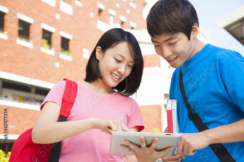 pretty woman using a tablet to discuss homework with a friend