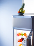 Fruit bowl and open refrigerator