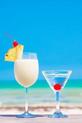 picture of two cocktails on a table near beach