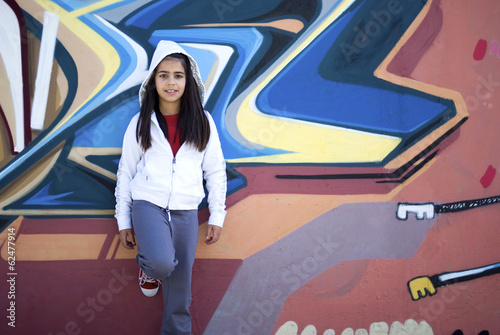 Girl standing against graffiti wall