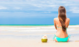 Happy young long haired woman in bikini with coconut on the