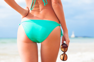 back view of fit young woman in green bikini with sunglasses in