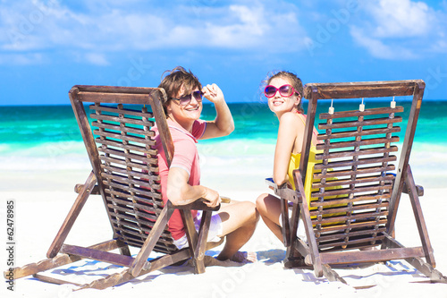 Couple in sunglasses on sun lounger on tropical beach smiling