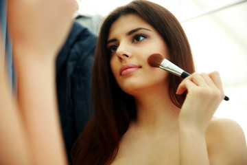 Young beautiful woman looking at mirror while doing makeup