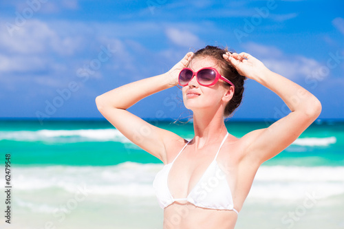 front view of beautiful young woman in bikini and sunglasses