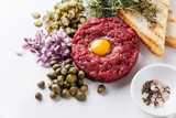 Beef tartare with capers and onion on white background