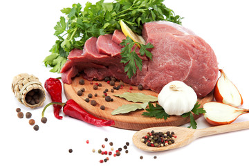 Raw meat, vegetables and spices on a wooden cutting board.