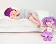 newborn baby girl sleeping in lilac knitted cap
