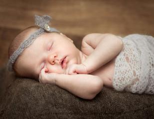 pretty  newborn girl sleeping on a cot