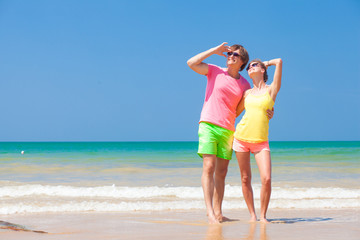 Couple in bright clothes on tropical beach looking at sky