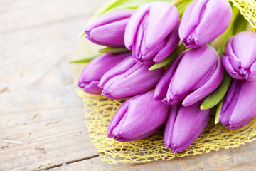Bouquet of purple tulips on wooden background
